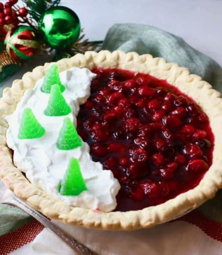 Christmas Cranberry Pie full of cranberry filling and topped with whipped cream and candy Christmas trees.