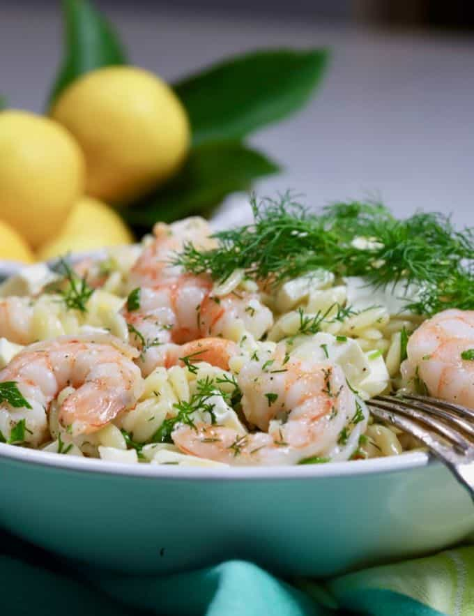 Shrimp pasta salad in a bowl with another bowl of lemons in the background.