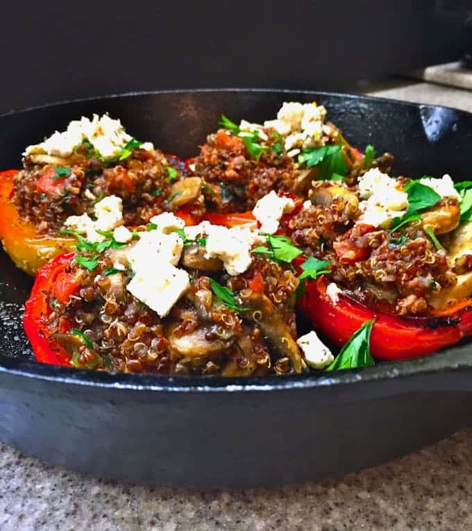 Peppers stuffed with quinoa in a cast iron skillet.
