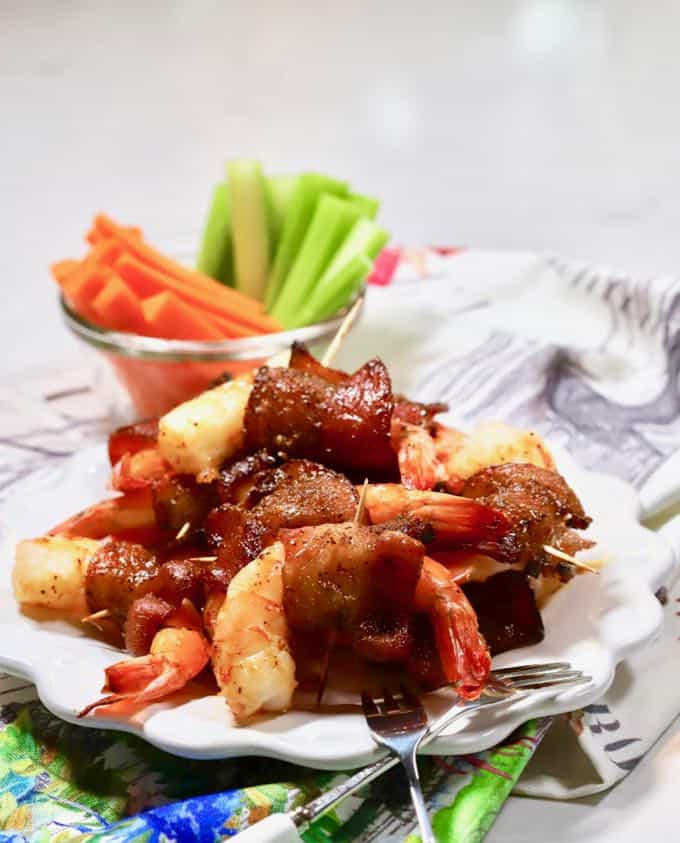 Bacon wrapped shrimp piled high on a white plate with celery and carrots in a bowl.