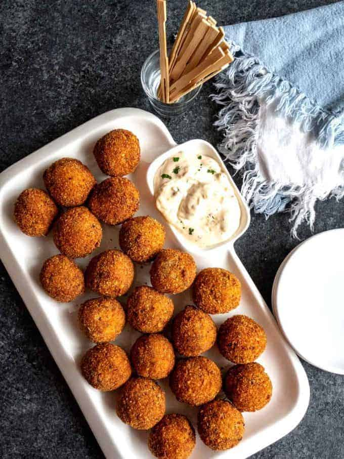 Cajun Pork Boulettes on a white serving plate with a dip.