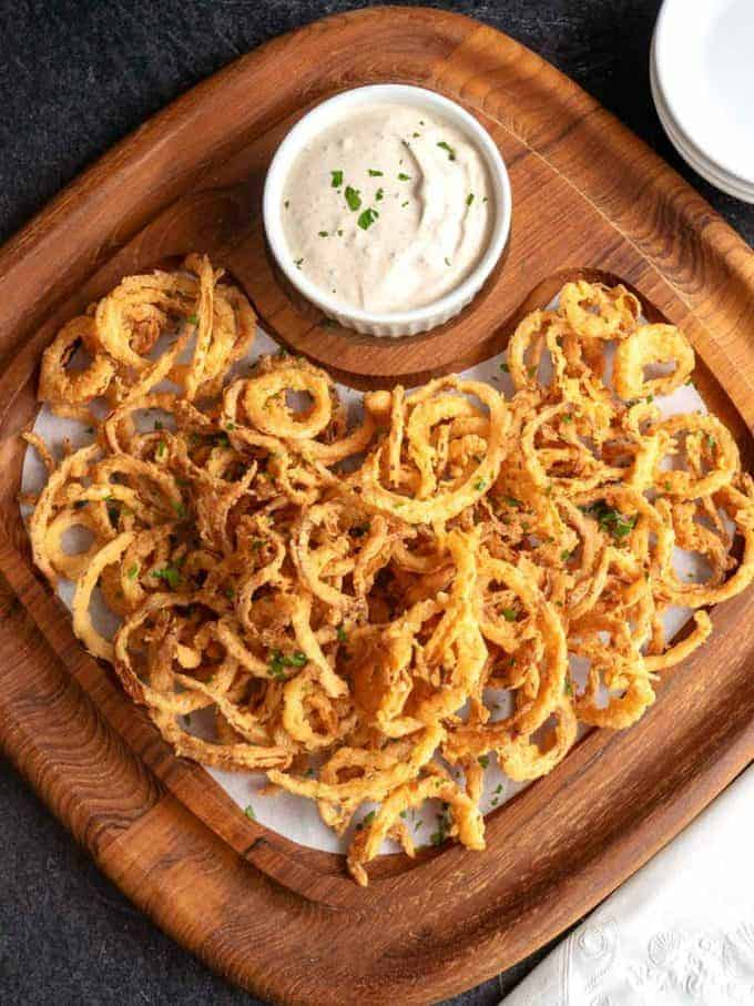 Cajun Onion Strings with a bowl of dipping sauce.