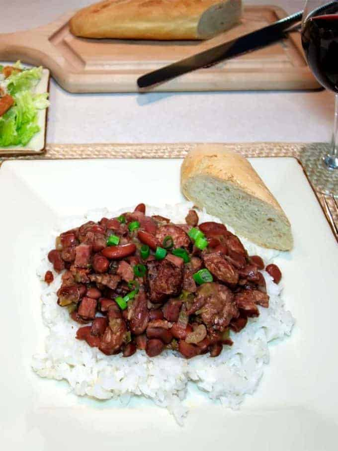 New Orleans Red Beans and Rice on a white plate with a piece of french bread.