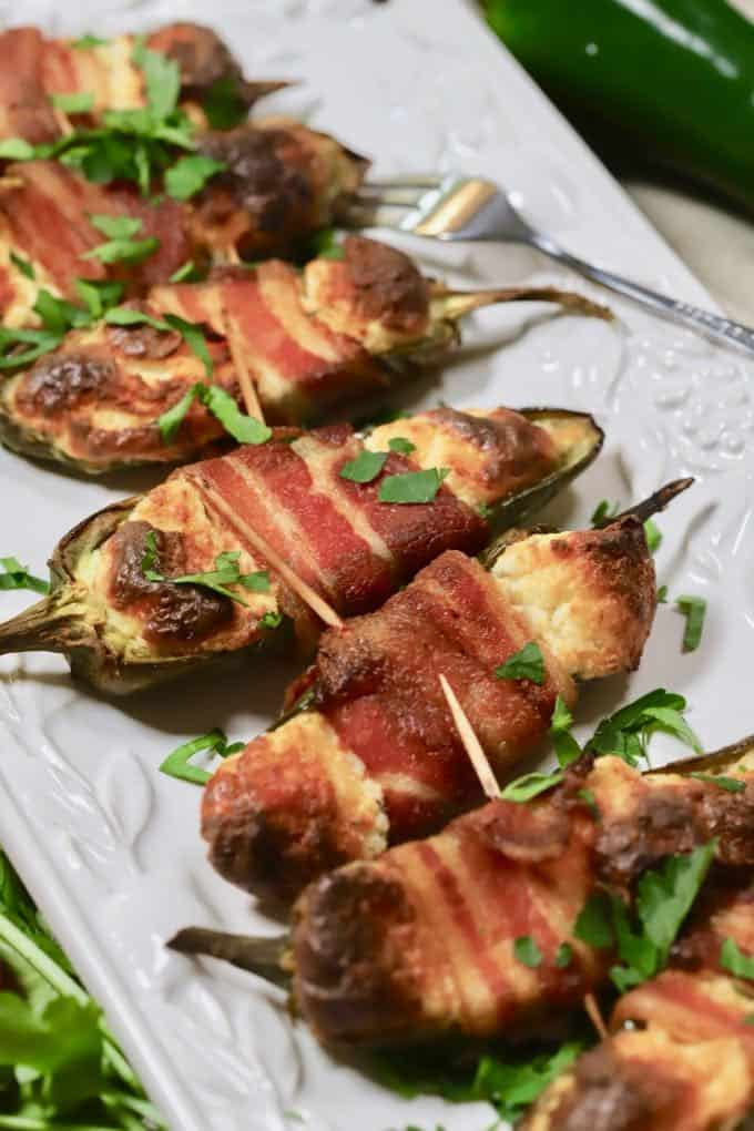 Game day appetizers, baked jalapeno poppers on a white serving platter.