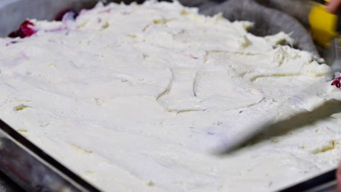 Spreading a whipped cream cheese topping over a dessert.