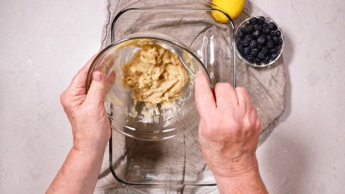 Pouring a butter and flour mixture into a clear glass baking dish.