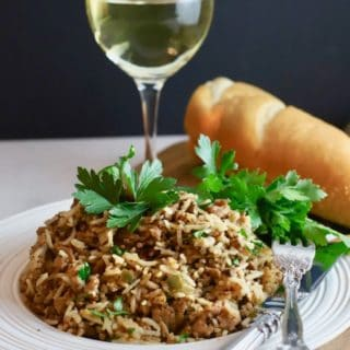 Dirty rice topped with parsley and a glass of wine.
