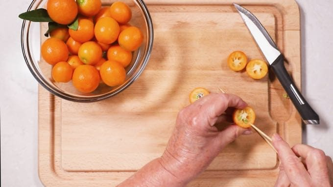 Removing seeds from a kumquat.