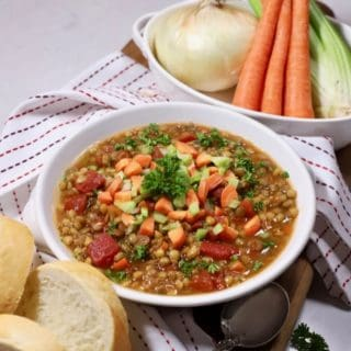 A white bowl full of lentil soup with carrots, celery and an onion in a bowl behind it.