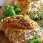 Stuffed chicken breasts on a wooden cutting board garnished with basil and rosemary.