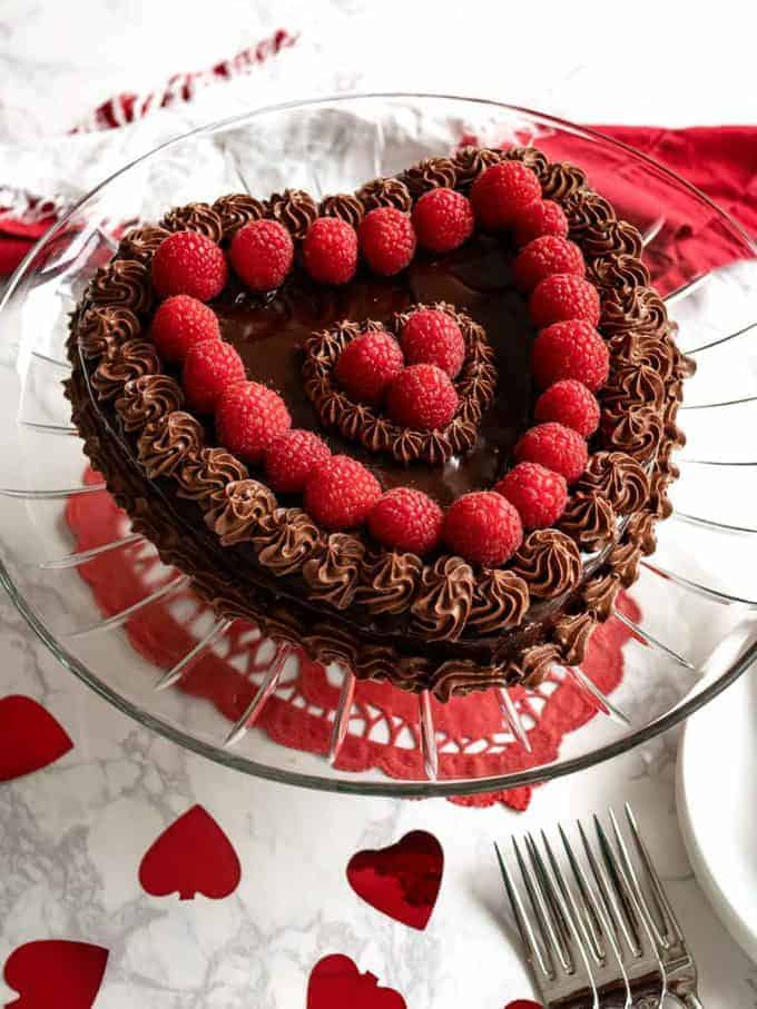 Flourless Chocolate Cake in the shape of a heart topped with raspberries.