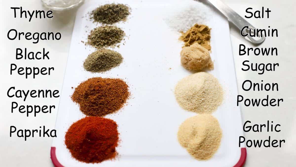Spices including oregano and thyme as well as garlic and onion powder and paprika on a board to make blackened seasoning.