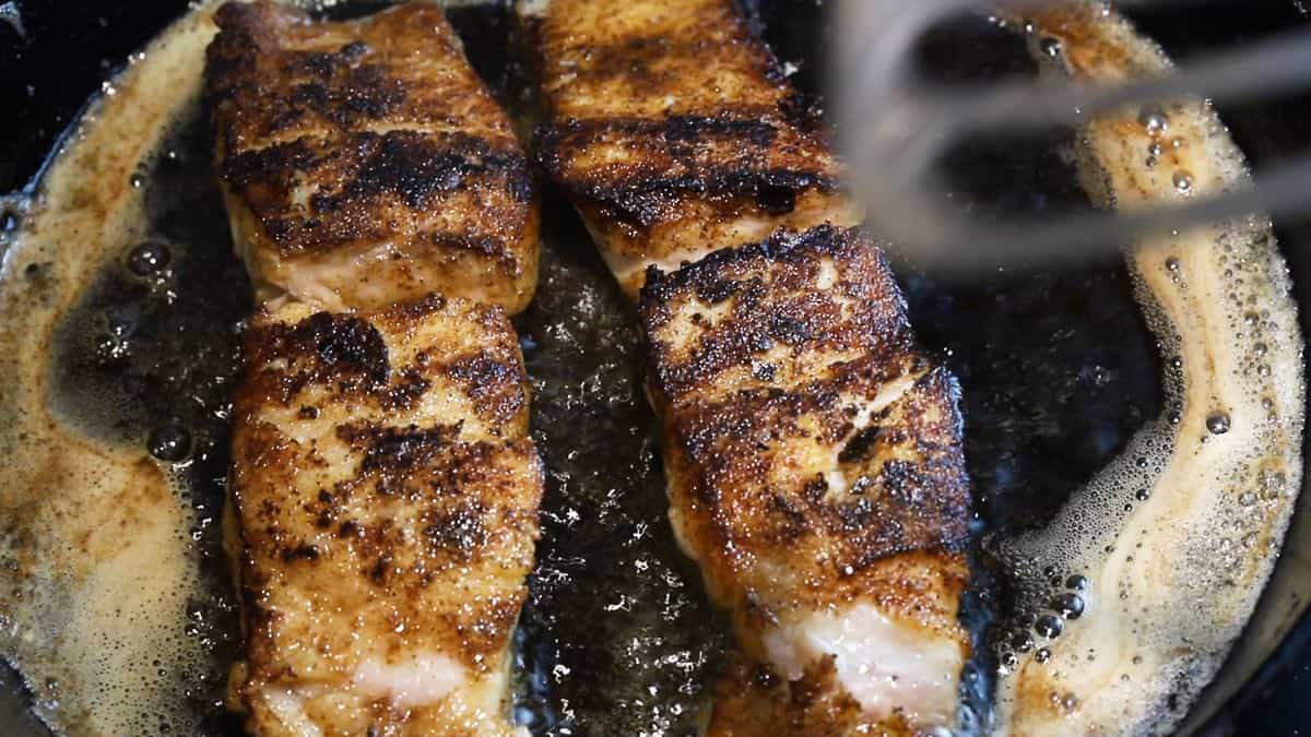 Two blackened fish fillets in a cast iron skillet.