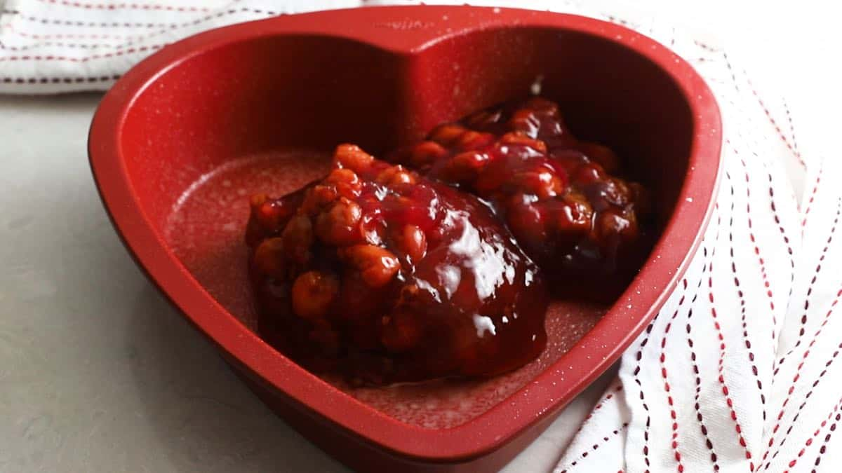 Cherry pie filling in a heart shaped baking pan.