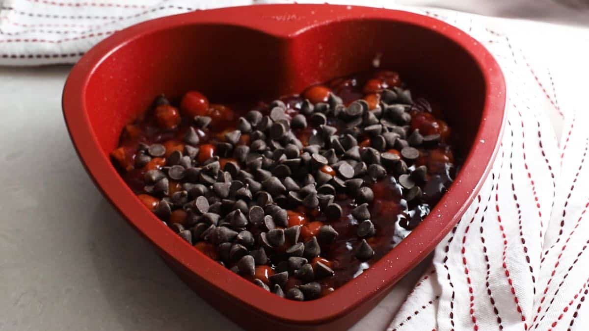 Chocolate chips over cherry pie filling in a red heart shaped baking pan.