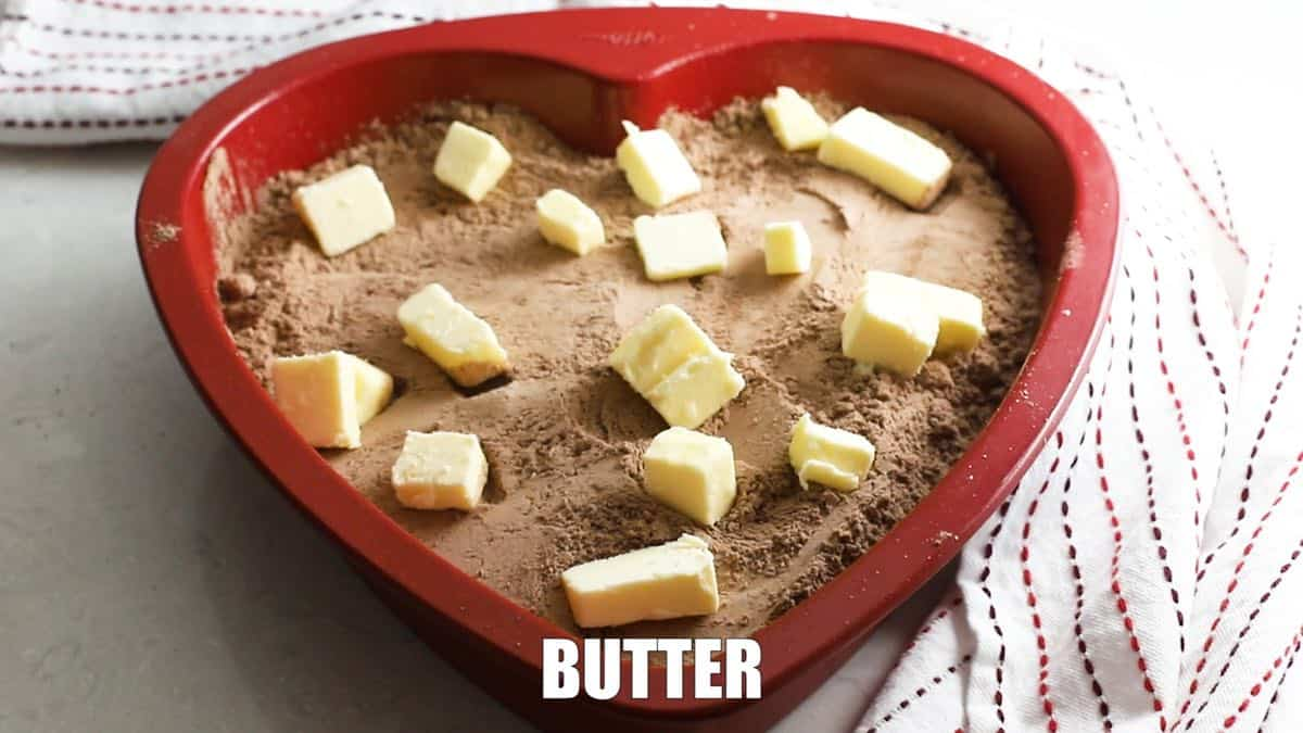 Cubes of butter on top of dry cake mix in a baking pan.