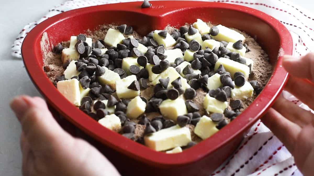Chocolate chips and cubes of butter on dry chocolate cake mix in a baking pan.
