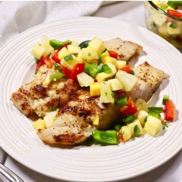 Two grouper fillets on a white plate topped with mango salsa.