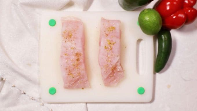 Two fish fillets topped with salt and pepper and other seasoning.