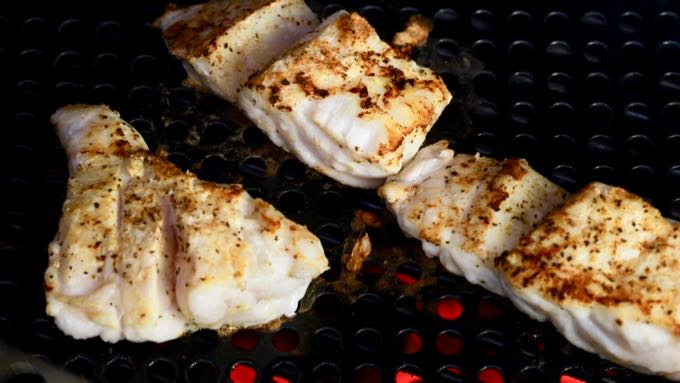 Three grouper fillets cooking on a grill.