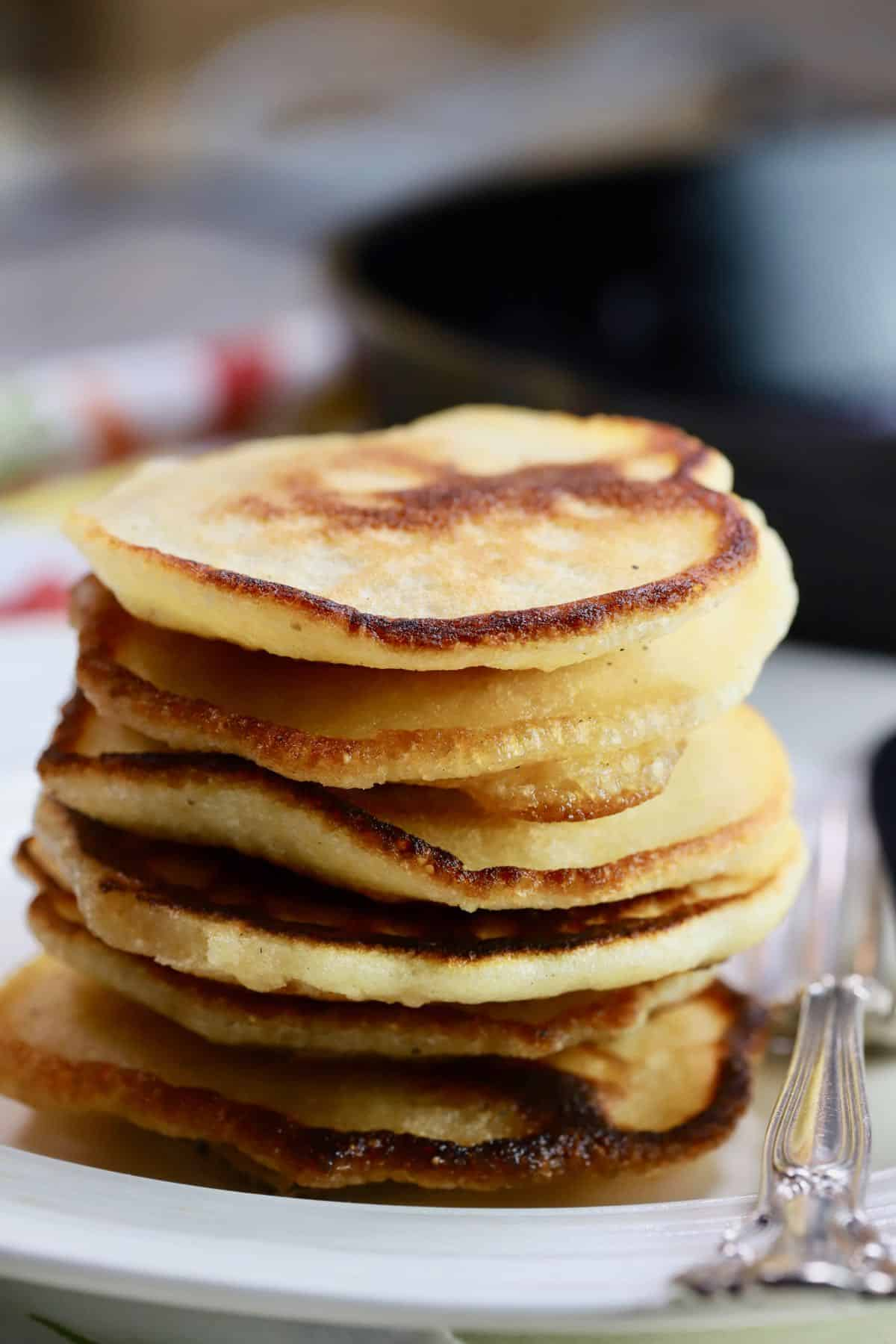 A stack of hoecakes on a white plate with a fork and knife.