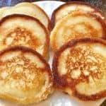 Six hoecakes or fried cornbread on a white plate.