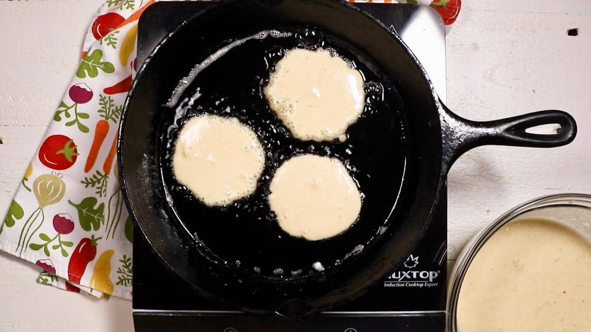 Cornmeal pancakes cooking in a cast-iron skillet.