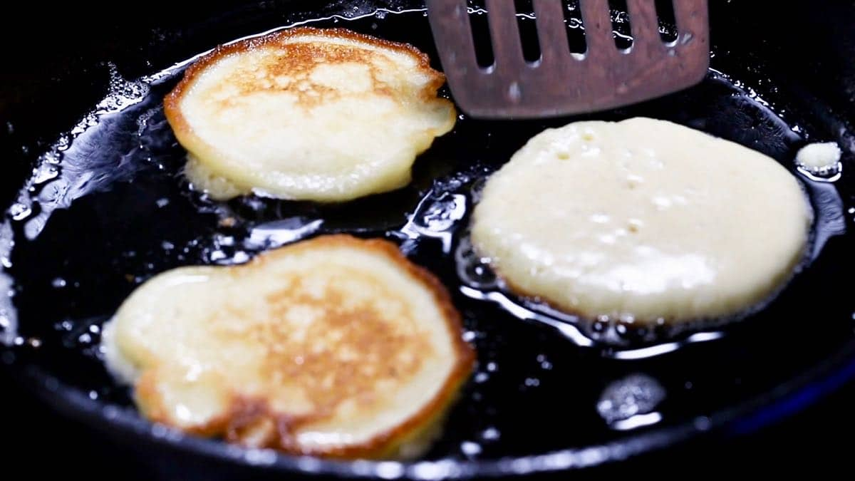 Cooking fried cornbread in a cast-iron skillet.