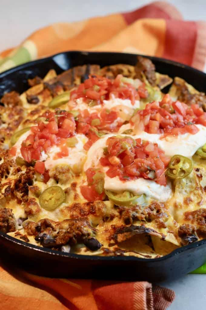 Nachos cooked in a cast-iron skillet and topped with sour cream and salsa.