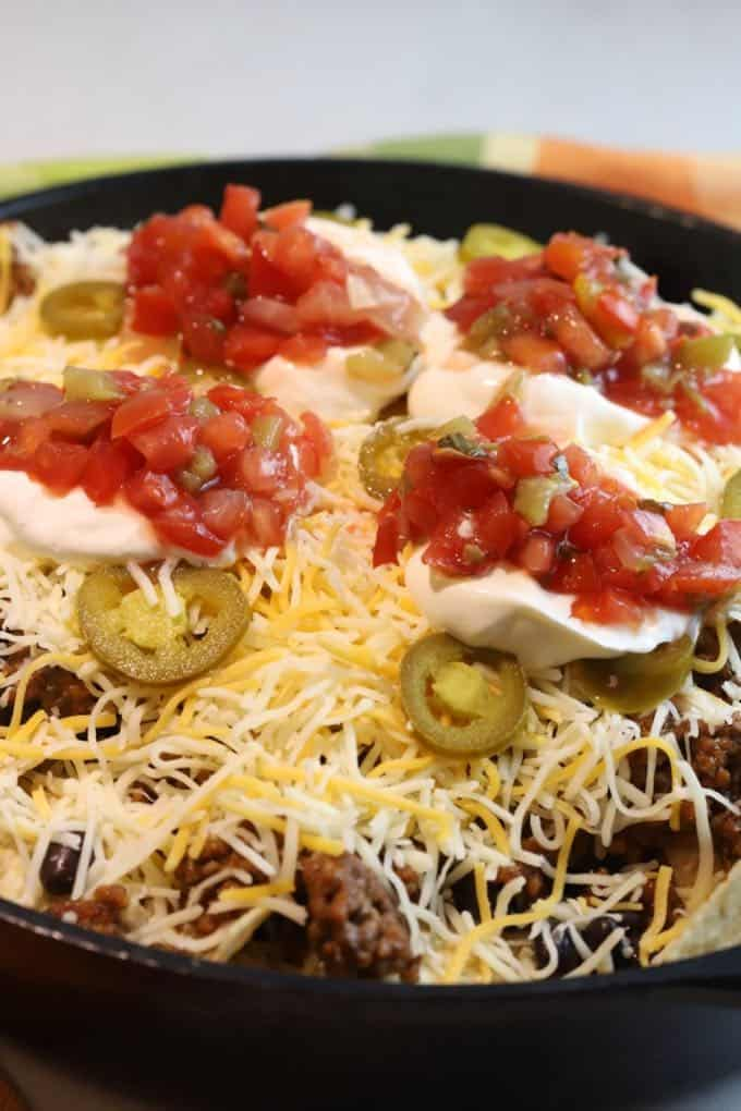 Nachos topped with cheese, jalapeños, sour cream, and salsa.