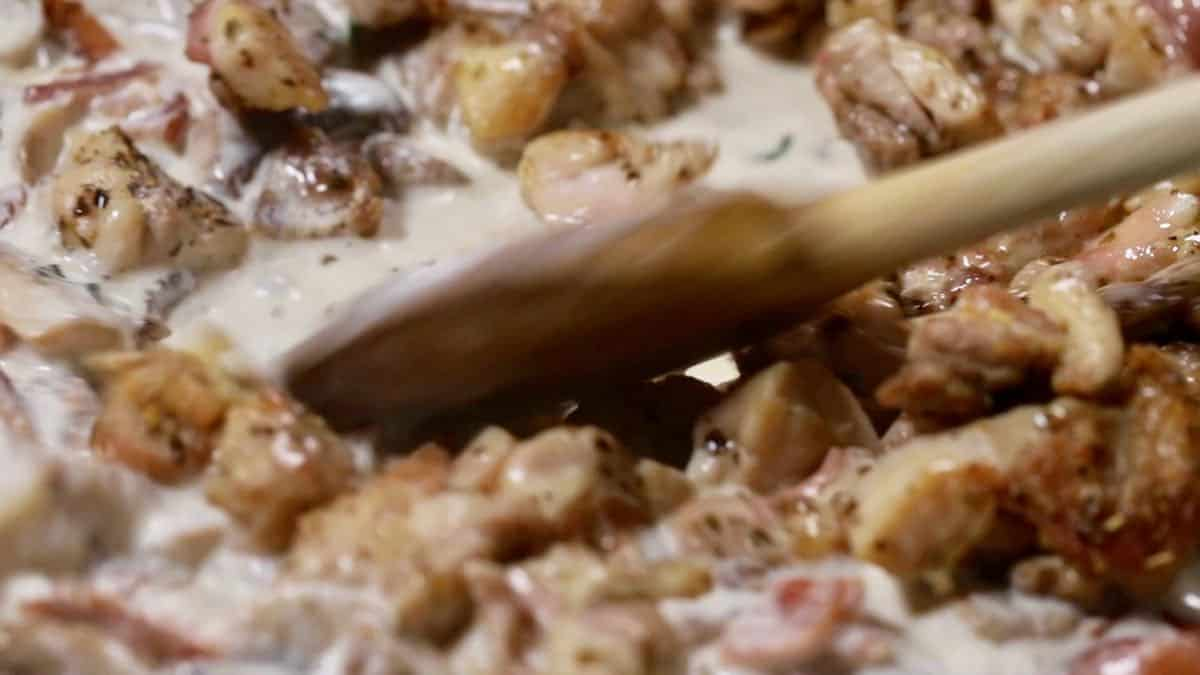 Chicken, bacon, mushroom cooking in heavy cream in a skillet.