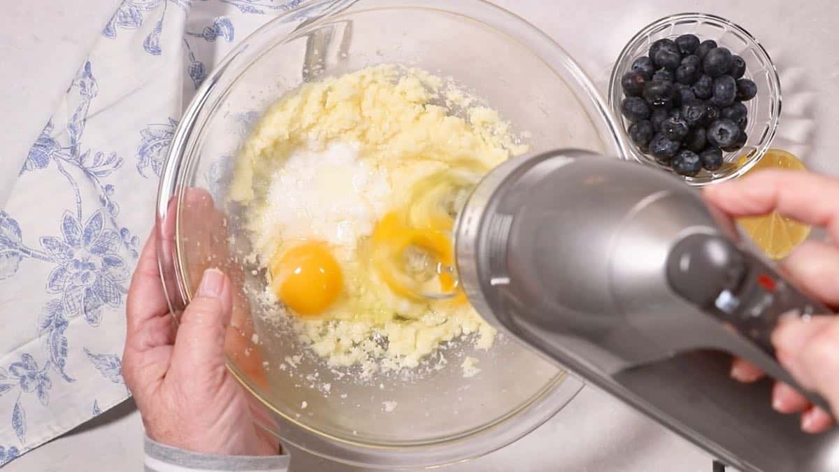 Sugar, butter, and eggs in a mixing bowl.