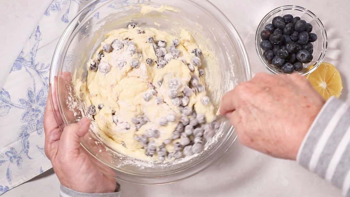 Stirring blueberries into bread batter in a clear glass mixing bowl.