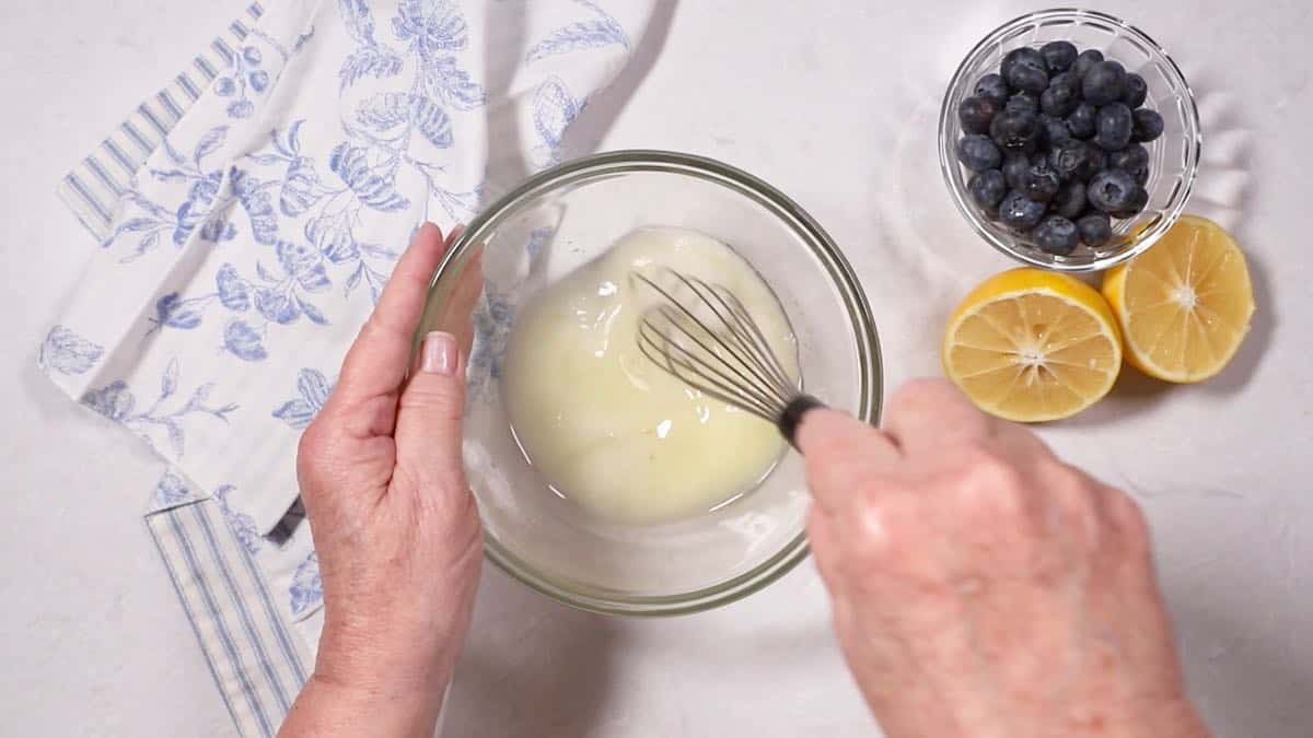 Whisking sugar and lemon juice in a bowl to make a glaze.