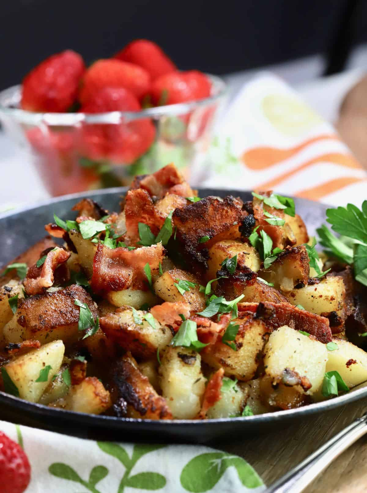 Southern fried potatoes served in a small cast iron skillet topped with bacon and parsley.