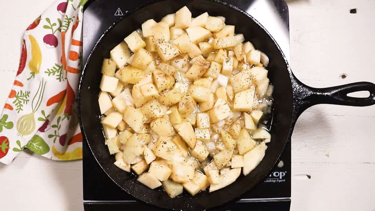 Fried potatoes in a cast-iron skillet cooking on the stove.