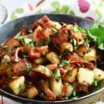 Crispy fried potatoes in a skillet topped with bacon.