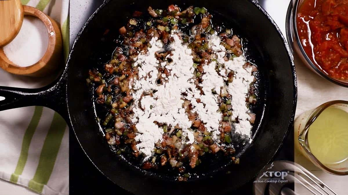 A cast iron skillet with peppers and onions and flour cooking.