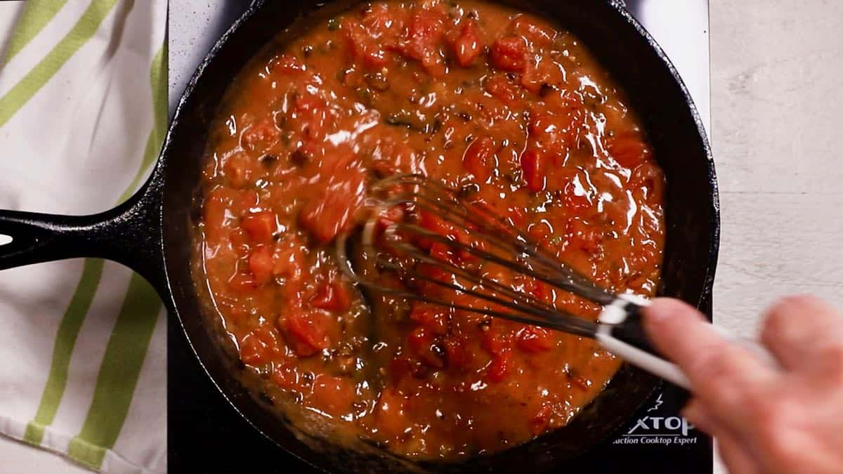 Tomato gravy cooking in a cast-iron skillet.