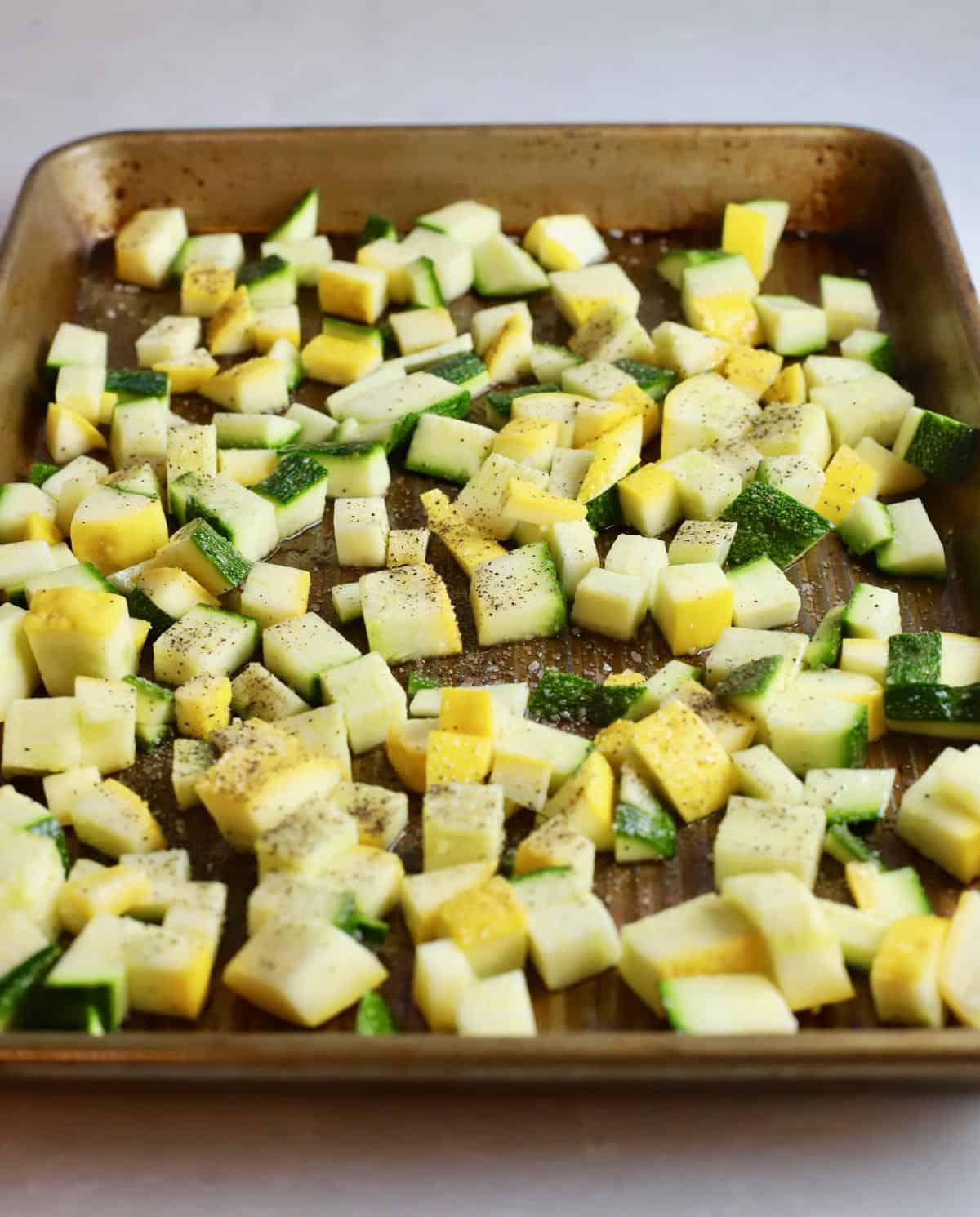 Chopped yellow and zucchini squash on a baking sheet.