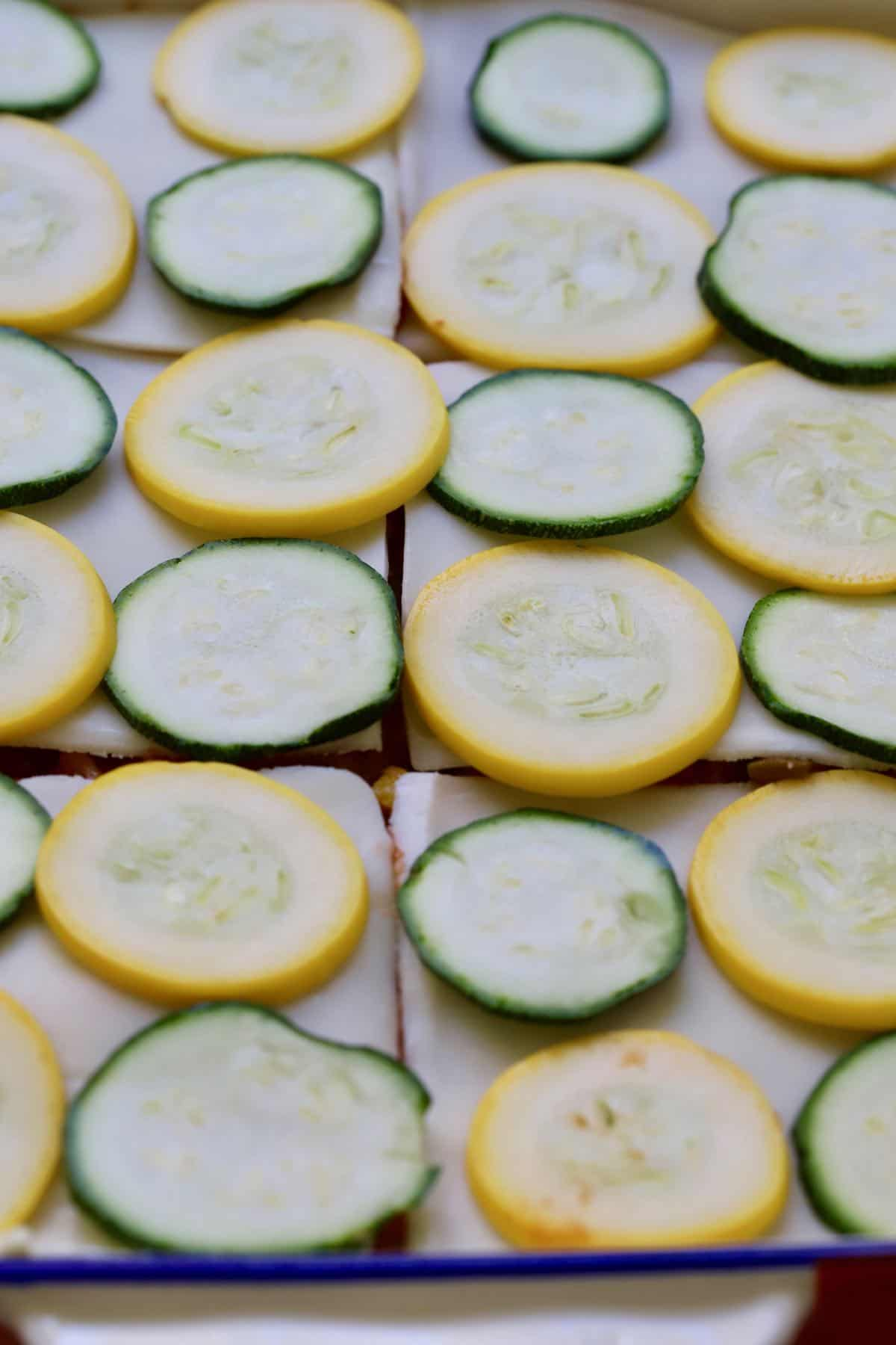 Sliced yellow and zucchini squash on top of mozzarella slices in a baking dish.