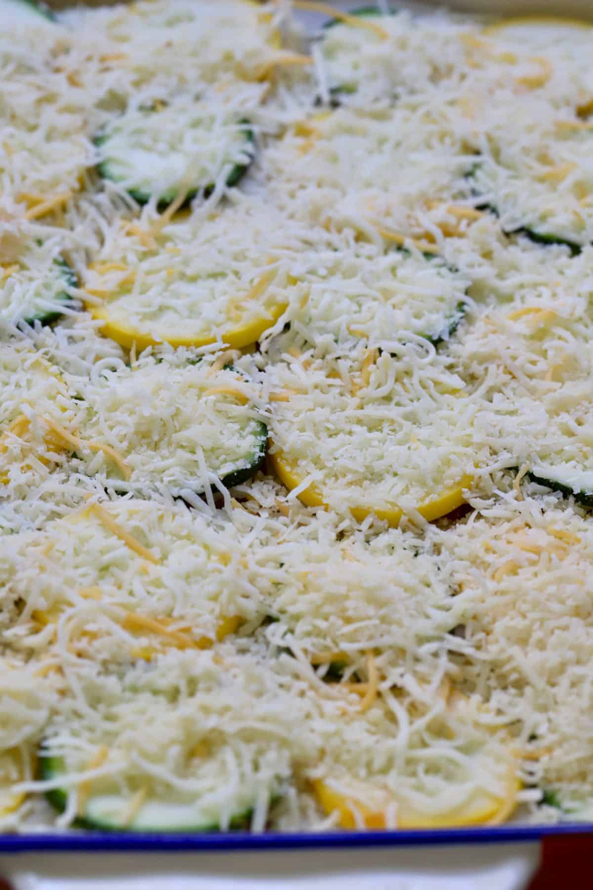 Mozzarella and parmesan cheeses covering slices of squash.