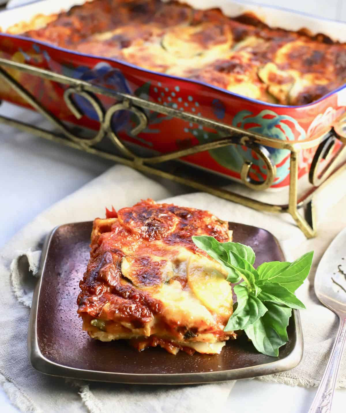 A pan of baked vegetable lasagna with a serving cut out.