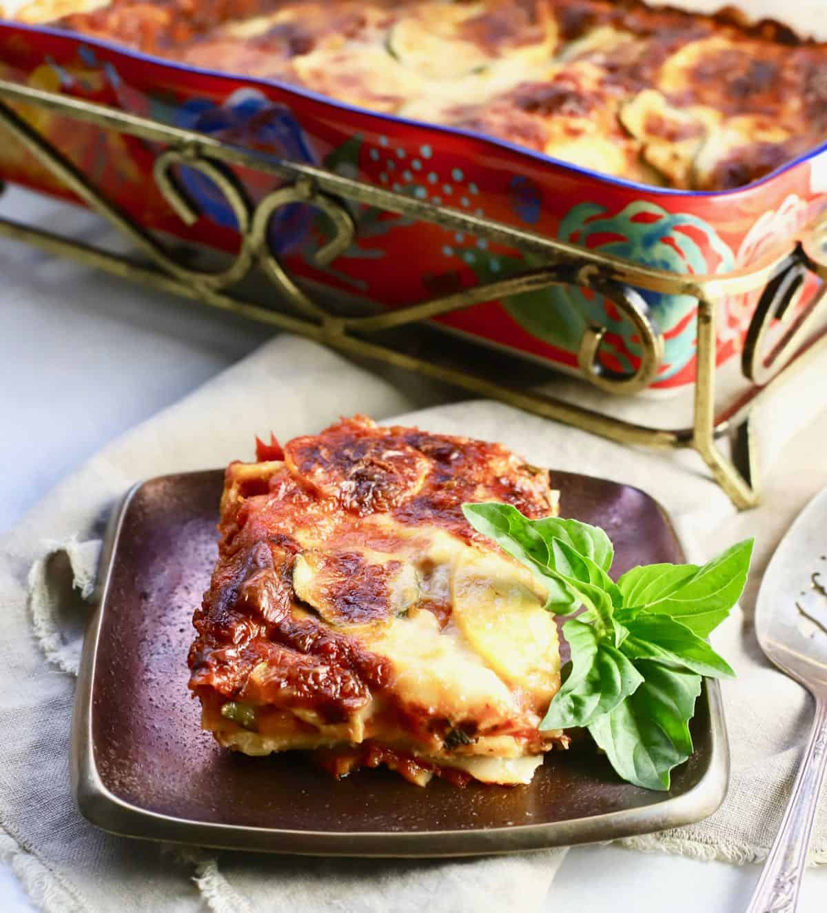 A serving of vegetable lasagna on a bronze plate.