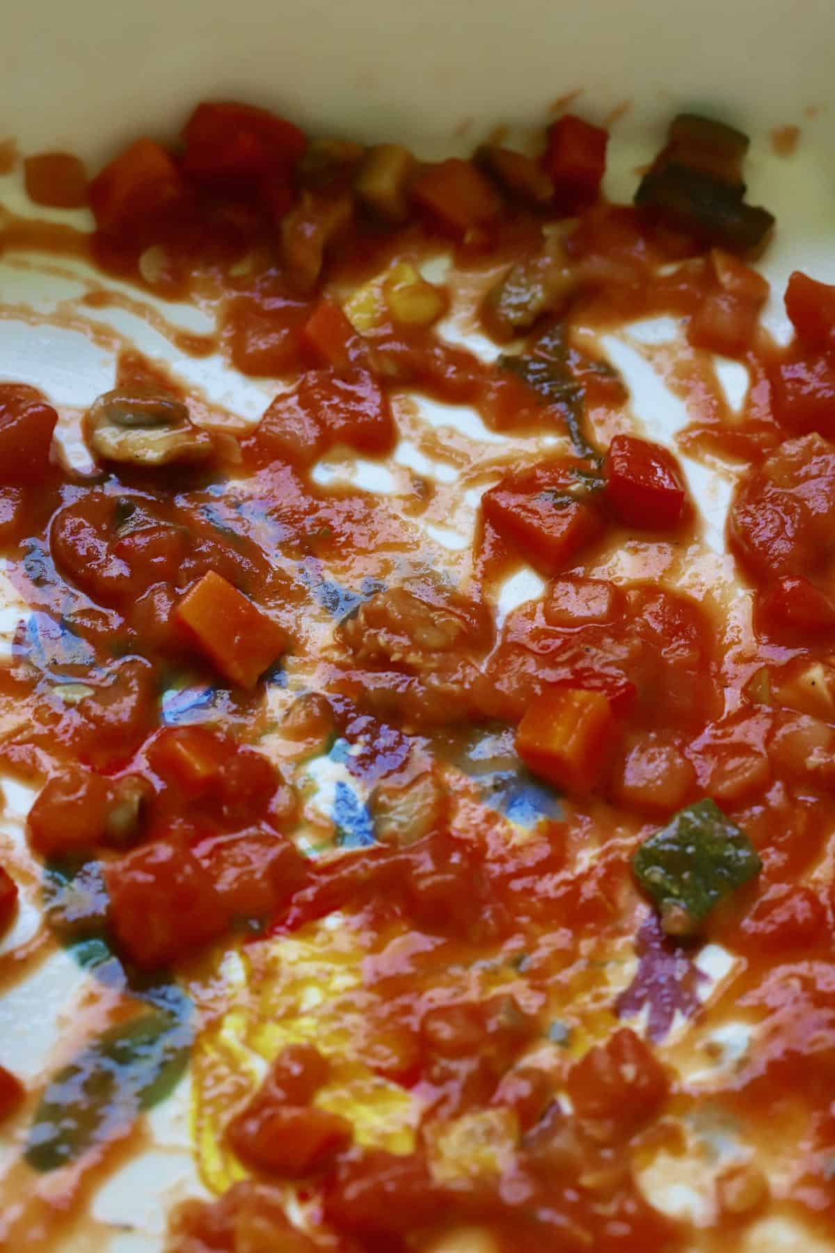Tomato sauce with vegetables in the bottom of a baking dish.