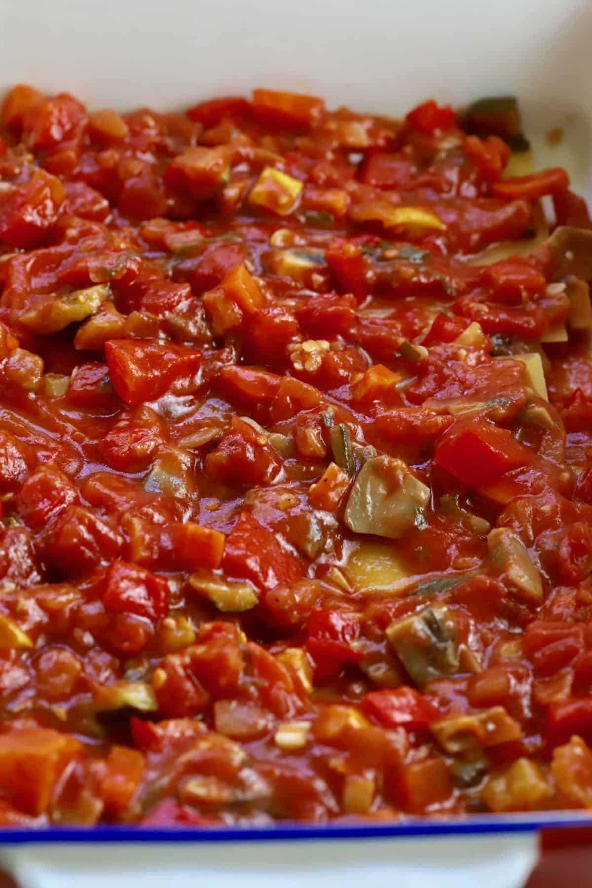 Tomato sauce with vegetables covering lasagna noodles in a baking dish.