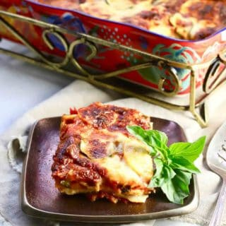 A brightly colored baking dish with lasagna and a slice of lasagna on a plate.