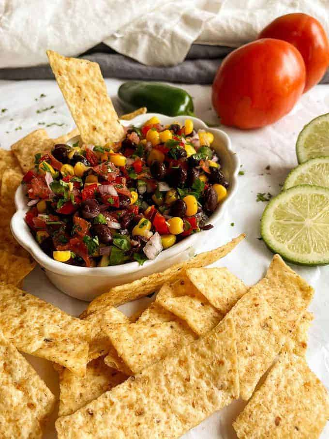 Black bean salsa in a dish next to tortilla chips.