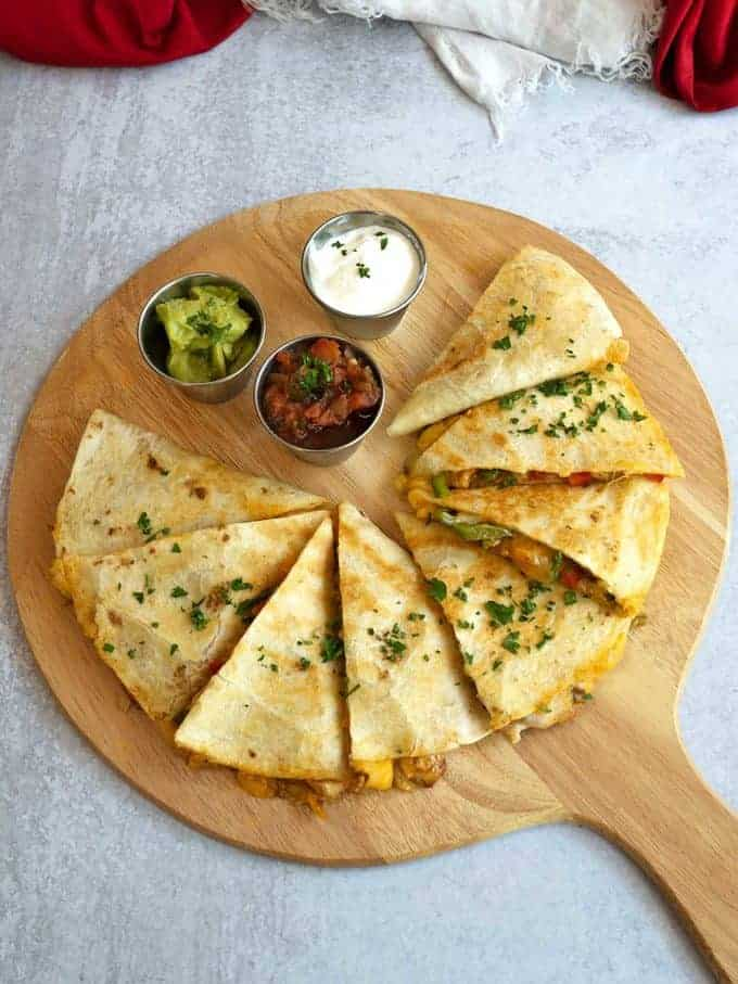 Chicken Fajita Quesadilla sliced on a wooden cutting board.