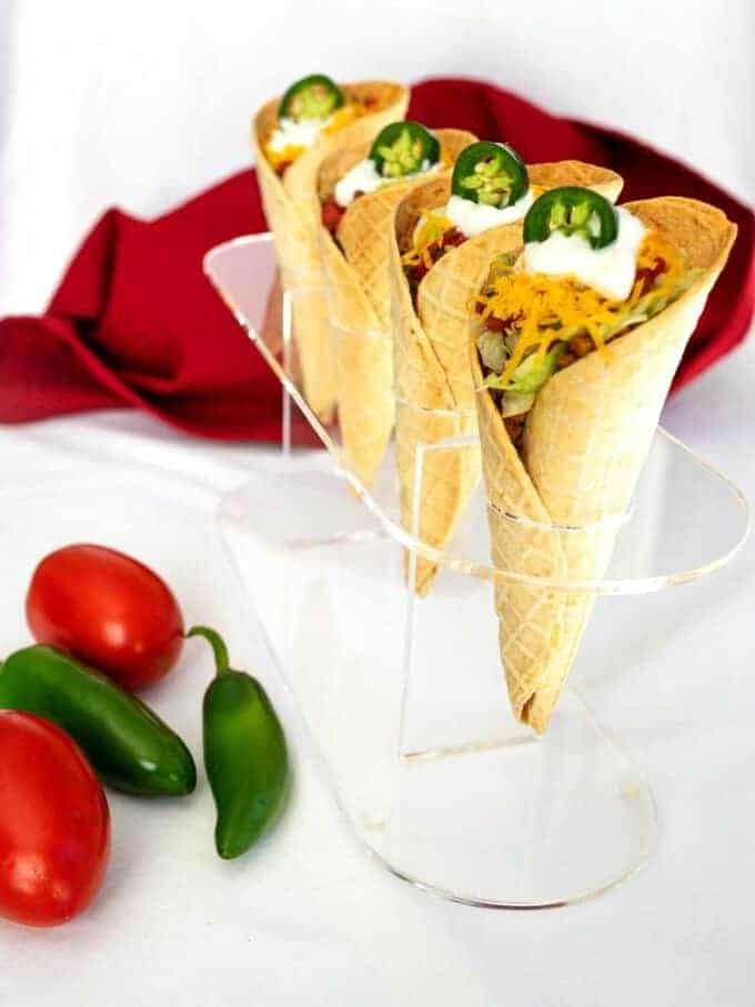 Four tacos in waffle cone taco shells.